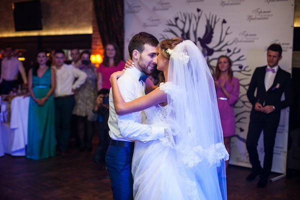 Beautiful newlywed couple first dance at wedding reception surrounded by smoke and blue lights