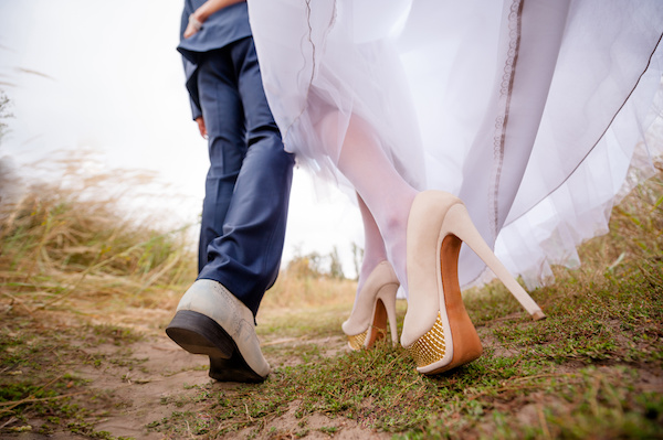 Legs brides and groom, newlyweds walk in the outdoors