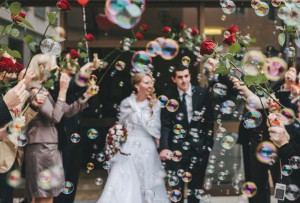 friends celebrating just married couple with soap bubbles and red roses